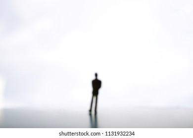 Intentional blurring image of human being standing alone in a vast space. The shot giving ideas of stranger, loneliness, depression, and decision.