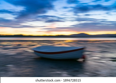 Intentional camera movement blur of colorful coastal evocative  intriguing impressionist style image in morning light with blue and golden hues.