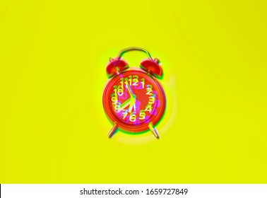 Intentional RGB distortion effect: a red alarm clock on a yellow surface, seen from above.