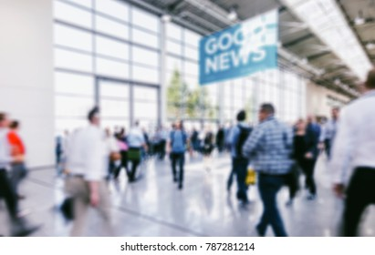 Intentionally blurred people walking trade show hall