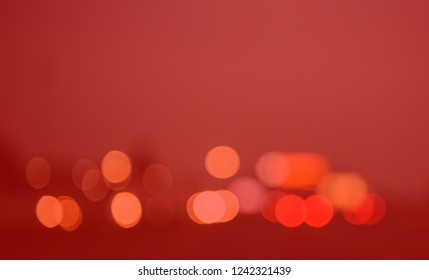 Intentionally blurred red toned bokeh city lights background effect. Abstract defocused traffic jam lights in modern city highway. Copy space. Christmas bokeh lights background