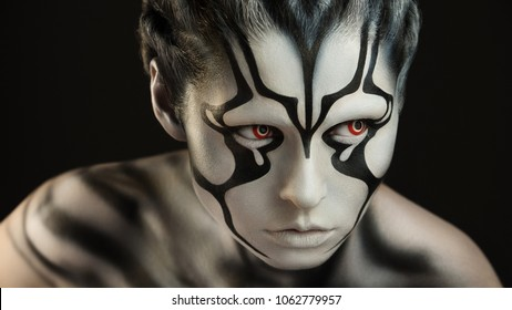 Intently and watchfully  looking alien creature with the brightly expressed red lenses and skin of black and white color created through a make-up