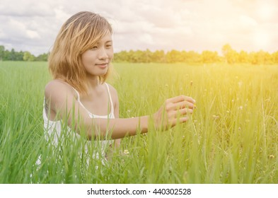 The interaction of man and nature (flower and hand).The girl guesses on a flower on nature in morning with sunrise