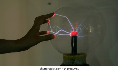 Interactive exposition in science museum. Woman touching plasma ball. Electricity and physics concept