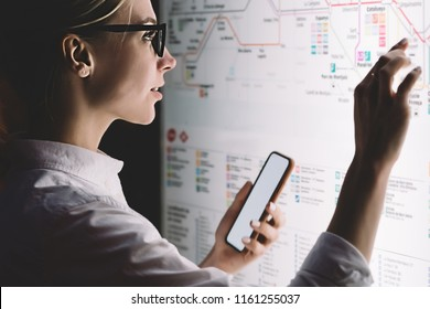 Interactive kiosk with public transport subway map.Female standing at big display with smartphone in hand.Young woman touching with finger screen while using train schedule application on mobile phone