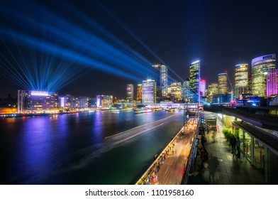 Interactive Lighting full color Laser Show at Vivid Festival 2018 in Sydney Harbour, Australia. Colorful lights illuminate Sydney Skyline at Circular Quay and numerous people enjoy the entertainment.
