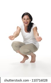An interactive portrait of an attractive, cheerful brunette mom kneeling down with arms outstretched as if gesturing for a hug toward the camera. Shot in the studio and isolated on a white background.