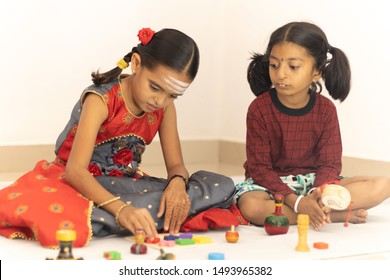 Interactively Two Indian children or little sisters happily playing with colorful wooden toys inside the home.