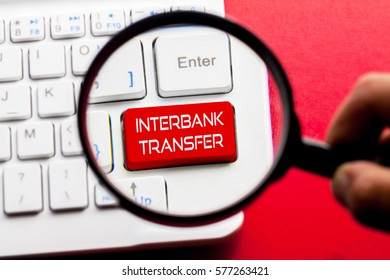 INTERBANK TRANSFER word written on keyboard view with magnifier glass