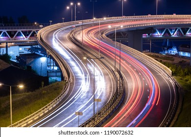 Interchange bridge road with car light streaks. Night light painting stripes. Long exposure photography.