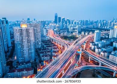 interchange of urban viaducts in nightfall with modern city skyline