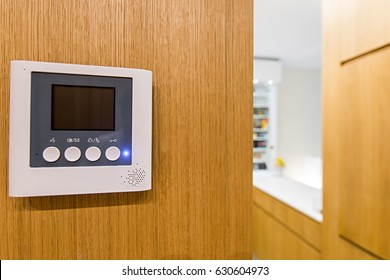Intercom video door bell on wooden wall in modern apartment