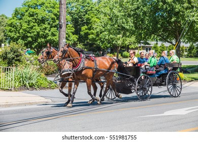 Intercourse, PA - June 12, 2016: An Amish wagon pulled by two horses on a village in Lancaster County.