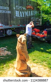 Intercourse, PA, USA - June 16, 2018: Using a chainsaw, a wood carver creates art from a log while demonstrating his craft to a crowd of visitors at the Intercourse Heritage Day festival.