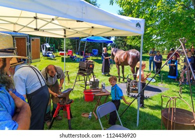 Intercourse, PA, USA - June 16, 2018: A local blacksmith demonstrates how to make shoes for a horse to the crowd of visitors at the Intercourse Heritage Day festival.