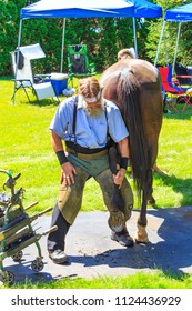 Intercourse, PA, USA - June 16, 2018: A local Amish farrier explains how to put shoes on a horse to a crowd of visitors at the Intercourse Heritage Day festival.
