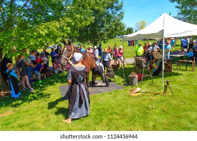 Intercourse, PA, USA - June 16, 2018: A local Amish farrier demonstrates the art of putting shoes on a horse to a crowd of visitors at the Intercourse Heritage Day festival.