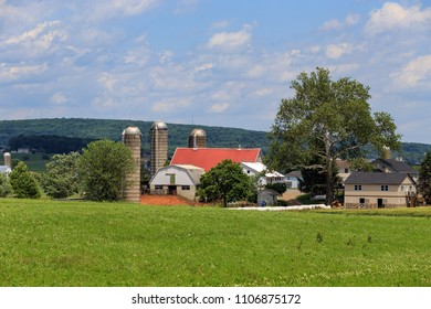 Intercourse, PA, USA - June 5, 2018: An Amish farm that included a barn with a red roof is located in Lancaster County, PA.