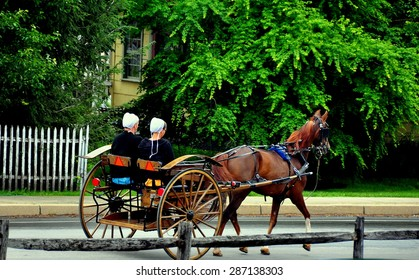 Intercourse, Pennsylvania - June 4, 2015:  Two Amish women riding in an open horse buggy on Queen Road  *