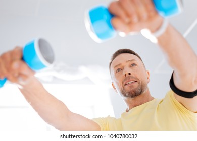 Interest in biohacking. Professional thoughtful pretty man working out with dumbbells while staring straight and taking care of health