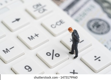 Interest rate cut percentage by FED, Federal Reserve concept, miniature people businessman thinking and looking at percent button on white calculator with background blur of US Dollar banknote.