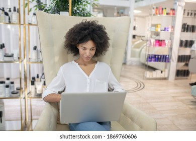 Interest, work. Attentive smiling young woman looking at laptop sitting in armchair in beauty center