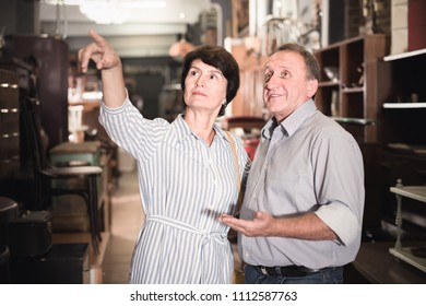interested adult woman with her husband are buying furniture for home in antique store