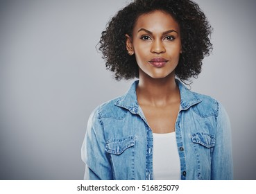 Interested beautiful black woman with blue jean shirt on gray background