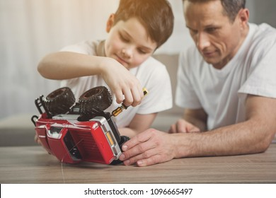 Interested boy is repairing toy by instrument with help of his dad. Focus on small red car