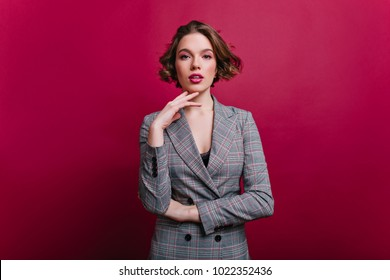 Interested businesswoman with trendy makeup posing on claret background. Indoor photo of serious young lady in tweed jacket standing in confident pose.