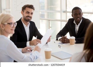 Interested diverse workers sit at table listen to female colleague talking, multiethnic business people look at employee share thoughts at briefing, curious mixed coworkers discuss project at meeting