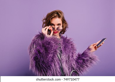 Interested girl in stylish purple fur coat looking to camera holding sparkle sunglasses. Indor portrait of confident female model with smartphone posing on bright background.