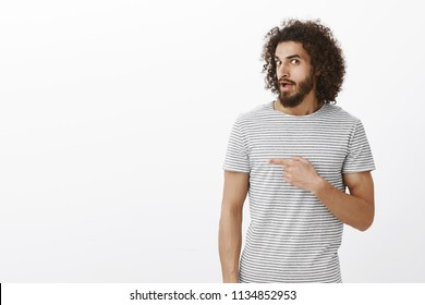 Interested hot hispanic guy with beard and afro hairstyle, turning at camera, pointing right while saying wow or asking question, being curious and questioned about person, spreading rumors