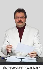 Interested man portrait near the desk on gray background