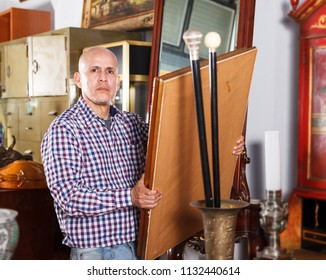 Interested mature man collector of vintage items choosing ancient things in antique store