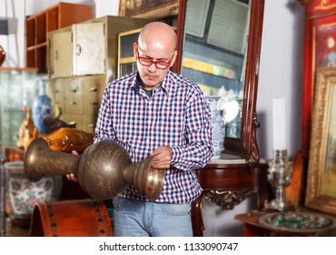 Interested mature man collector of vintage goods choosing ancient things in antique shop