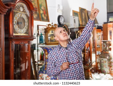 Interested middle aged male pointing at vintage goods at antiques shop