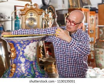Interested modern man measuring vintage amphora in shop of antique goods