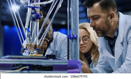 Interested multiethnic scientists gathering around 3-D printer and watching process of model production in laboratory.
