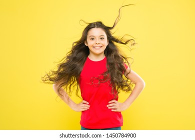 Interested in my hair and my hairdresser. Happy small girl child smiling with flowing long brunette hair on yellow background. Kids hairdresser. Hairdresser salon.