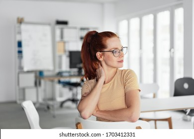 Interested young female office worker wearing glasses watching outdoors through the window as she relaxes on a reversed chair during her break