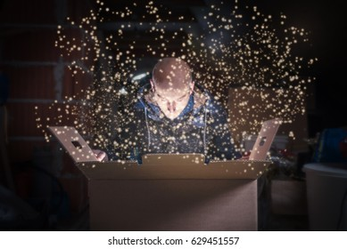 Interested young man is opening a large cardboard box with something magic and exciting inside it on attic