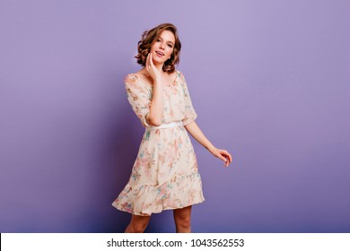 Interested young woman in cute dress gently touching her face on purple background. Indoor photo of lovable white lady with curly hair dancing in studio.
