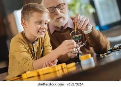Interesting activity. Joyful positive boy sitting together with his grandfather and looking at the microscheme while working with him