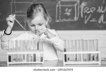 Interesting approach to learn. Future scientist. Explore and investigate. School lesson. Girl cute school pupil play with test tubes and colorful liquids. School chemical experiment. School education.