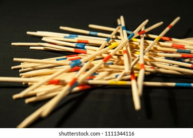 An interesting board game of Mikado for everyone with wooden sticks on a black background