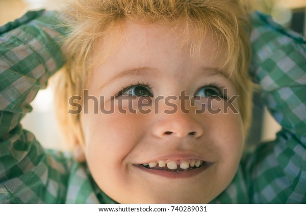 Interesting boy face of adorable little kid. Positive and scincere emotions from happy child. Child's happiness, smile of little boy. Cute boy raised hands and carelessly laughs