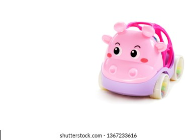 Interesting bright toy pink rattle on isolated background with copy space. Pink fun car close up with selective focus.