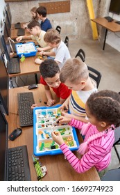 Interesting building kit for kids on table with computers. From above view of boys and girls creating toys. Science engineering. Nice interested friends chatting and working on project together.