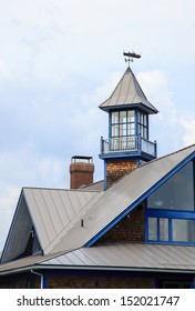 An interesting building with metal peaked roofs, a look out tower and ship weather vane.